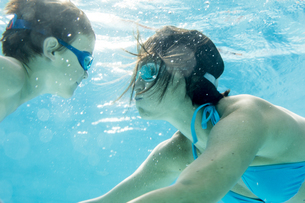 Boy diving underwater with his mum, swimming poolの写真素材 [FYI04357230]