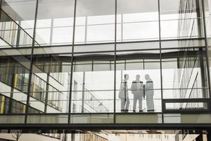 Three businessmen behind glass facadeの写真素材 [FYI04357231]