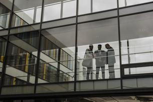 Three businessmen behind glass facadeの写真素材 [FYI04357232]