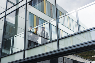 Three businessmen behind glass facade, passageの写真素材 [FYI04357234]