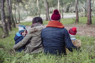 Rear view of family sitting in forestの写真素材 [FYI04357377]