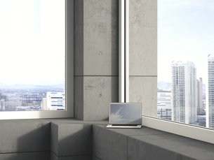Laptop standing on window sill in a modern high-rise buildinの写真素材 [FYI04357853]