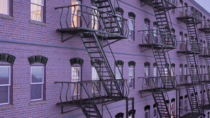 Facade of multi-family house with fire escape staircases atのイラスト素材 [FYI04357982]