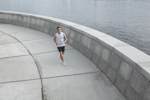 Young man running at the riverbankの写真素材 [FYI04358649]