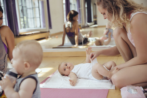 Mother changing diapers of baby in exercise roomの写真素材 [FYI04358789]