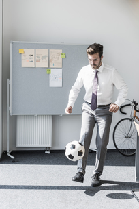 Businessman playing football in officeの写真素材 [FYI04358925]