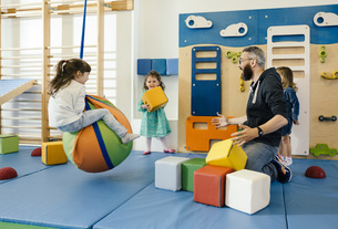 Pre-school teacher and happy children playing in gym room inの写真素材 [FYI04359258]