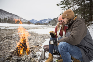 Couple on a trip in winter having a break at camp fireの写真素材 [FYI04359786]