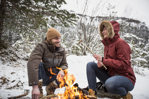 Happy couple on a trip in winter having a break at camp fireの写真素材 [FYI04359788]