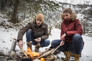 Couple on a trip in winter having a break at camp fireの写真素材 [FYI04359789]