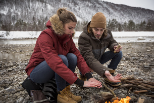 Couple on a trip in winter warming hands at camp fireの写真素材 [FYI04359790]