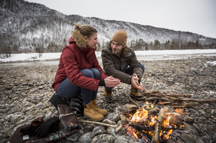 Couple on a trip in winter warming hands at camp fireの写真素材 [FYI04359791]