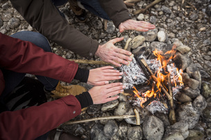 Close-up of couple warming hands at camp fireの写真素材 [FYI04359792]