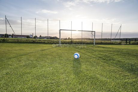 Ball lying on football ground at sunsetの写真素材 [FYI04360821]
