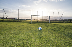 Ball lying on football ground at sunsetの写真素材 [FYI04360821]
