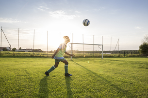 Young football player heading the ball on football ground atの写真素材 [FYI04360823]
