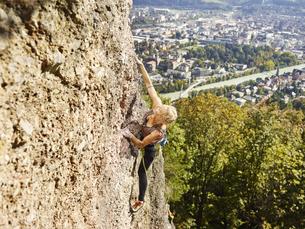 Austria, Innsbruck, Hoettingen quarry, woman climbing in rocの写真素材 [FYI04362424]