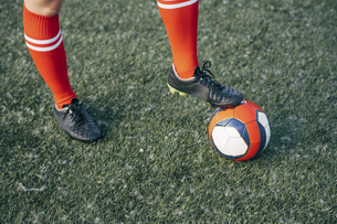 Legs of a woman standing on football ground with the ballの写真素材 [FYI04362755]