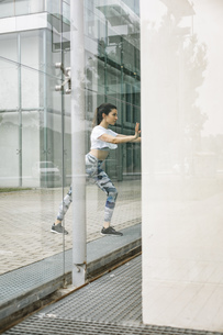 Young woman doing stretching exercise at glass facadeの写真素材 [FYI04364460]