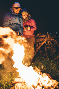 Couple with with bikes standing at camp fire looking at flamの写真素材 [FYI04364526]