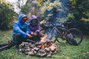 Laughing couple with with bmx bikes sitting at camp fire griの写真素材 [FYI04364529]