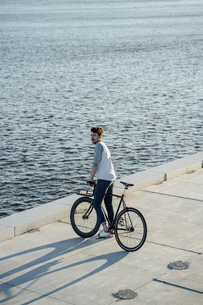 Young man with commuter fixie bike having a break at the rivの写真素材 [FYI04364681]