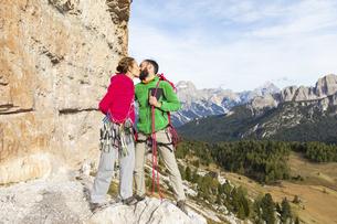 Italy, Cortina d'Ampezzo, couple with climbing equipment kisの写真素材 [FYI04364884]