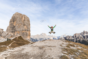 Italy, Cortina d'Ampezzo, happy hiker jumping at the top ofの写真素材 [FYI04364885]