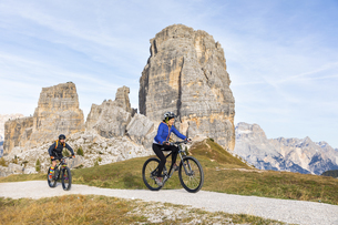 Italy, Cortina d'Ampezzo, two people cycling with mountain bの写真素材 [FYI04364886]