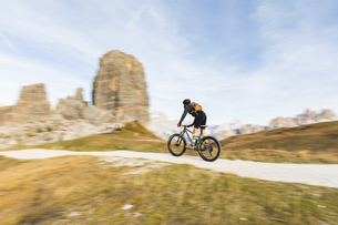 Italy, Cortina d'Ampezzo, panning view of man cycling with mの写真素材 [FYI04364887]
