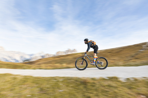 Italy, Cortina d'Ampezzo, panning view of man cycling with mの写真素材 [FYI04364888]