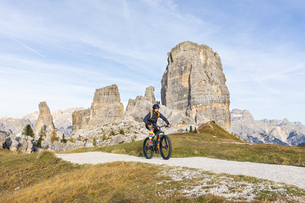 Italy, Cortina d'Ampezzo, man cycling with mountain bike inの写真素材 [FYI04364890]
