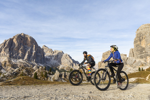 Italy, Cortina d'Ampezzo, two people cycling with mountain bの写真素材 [FYI04364891]