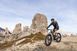 Italy, Cortina d'Ampezzo, man cycling with mountain bike inの写真素材 [FYI04364892]