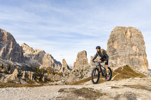 Italy, Cortina d'Ampezzo, man cycling with mountain bike inの写真素材 [FYI04364893]