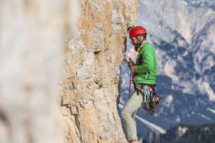 Italy, Cortina d'Ampezzo, man securing the rope while climbiの写真素材 [FYI04364902]