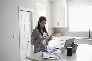 Woman electronically depositing check with smart phone in kitchenの写真素材 [FYI04366353]