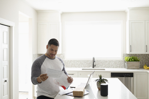 Man paying bills at laptop in kitchenの写真素材 [FYI04366356]