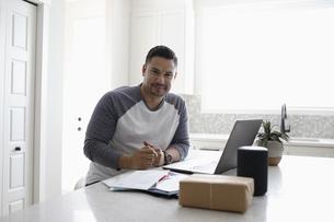 Portrait confident man paying bills at laptop in kitchenの写真素材 [FYI04366359]