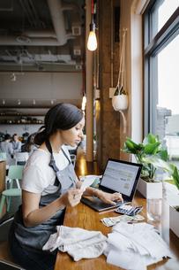 Restaurant owner calculating receiptsの写真素材 [FYI04368046]