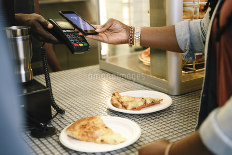 Young woman paying for pizza with smart phoneの写真素材 [FYI04368720]