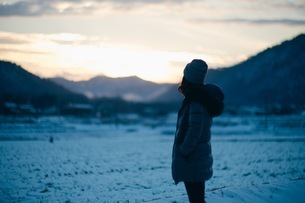 Side View Of Woman Standing On Snowcapped Fieldの写真素材 [FYI04369548]
