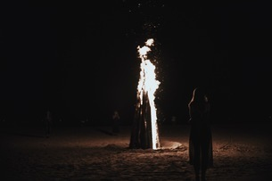 Rear View Of Woman Standing By Camp Fire On Beachの写真素材 [FYI04370584]