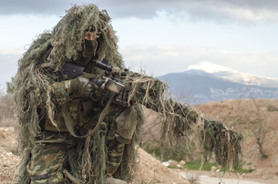 Sniper Holding Rifle Against Skyの写真素材 [FYI04370912]