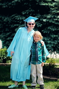 Full Length Portrait Of Smiling Graduate With Brother On Fieldの写真素材 [FYI04372173]