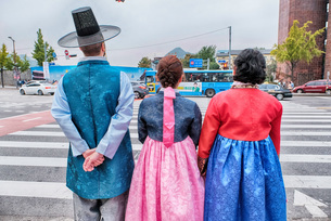 Rear View Of Family In Korean Traditional Clothing Standing On City Streetの写真素材 [FYI04374906]