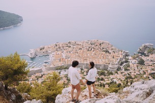 Rear View Of Couple Enjoying The View Of A Croatian Village On The Seaの写真素材 [FYI04375118]