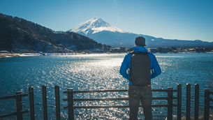 Rear View Of Man Standing By Lake Against Mt Fuji In Winterの写真素材 [FYI04375468]
