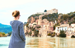 Rear View Of Woman Standing By Ebro River Against Miravet Villageの写真素材 [FYI04377720]