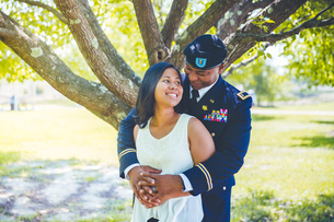 Smiling Soldier Embracing Woman While Standing Against Trees At Parkの写真素材 [FYI04379890]